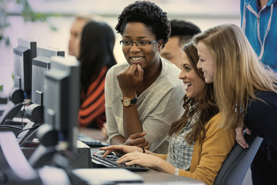 group of young women on a desktop computer